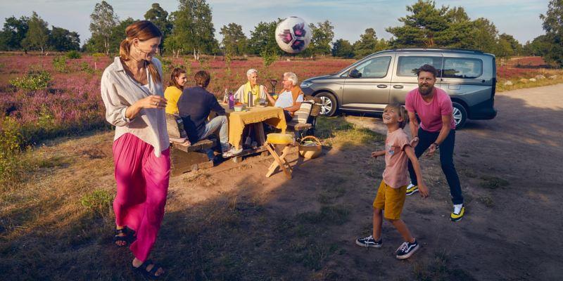 Le VW Caddy Combi à côté d'une famille qui pique-nique.