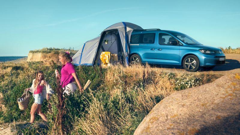 Bildet viser en blå Volkswagen Caddy California minicamper med telt, campingstoler og campingbord. To unge jenter løper ned til stranden i sommerklær