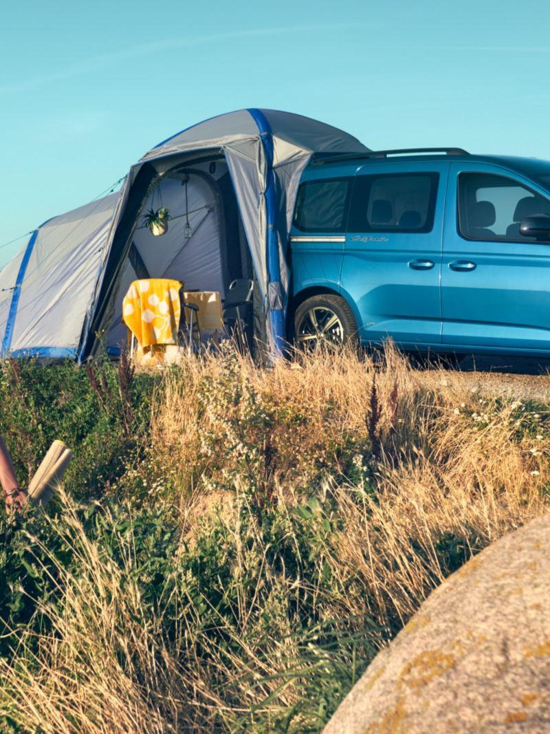 Bildet viser en blå Volkswagen Caddy California Maxi mini camper som står parkert ved stranda og et campingtelt