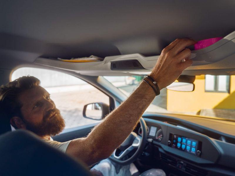 Мужчина кладет мелкую поклажу на полку над лобовым стеклом в новом Volkswagen Caddy Kombi