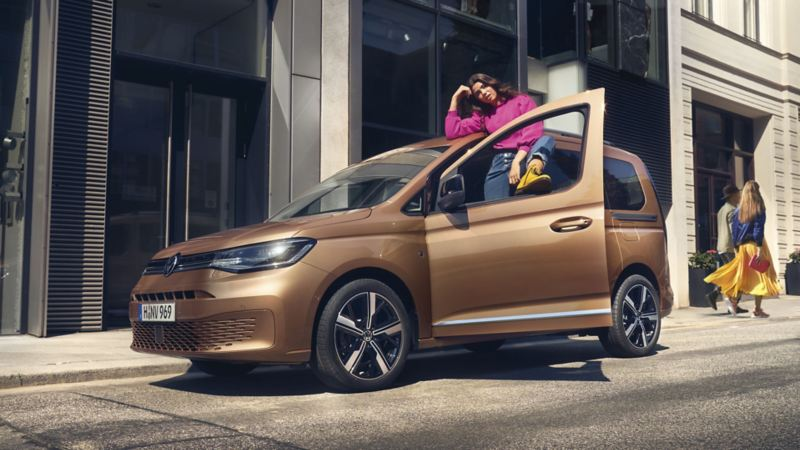 Una ragazza appoggiata al suo Nuovo Caddy Volkswagen.