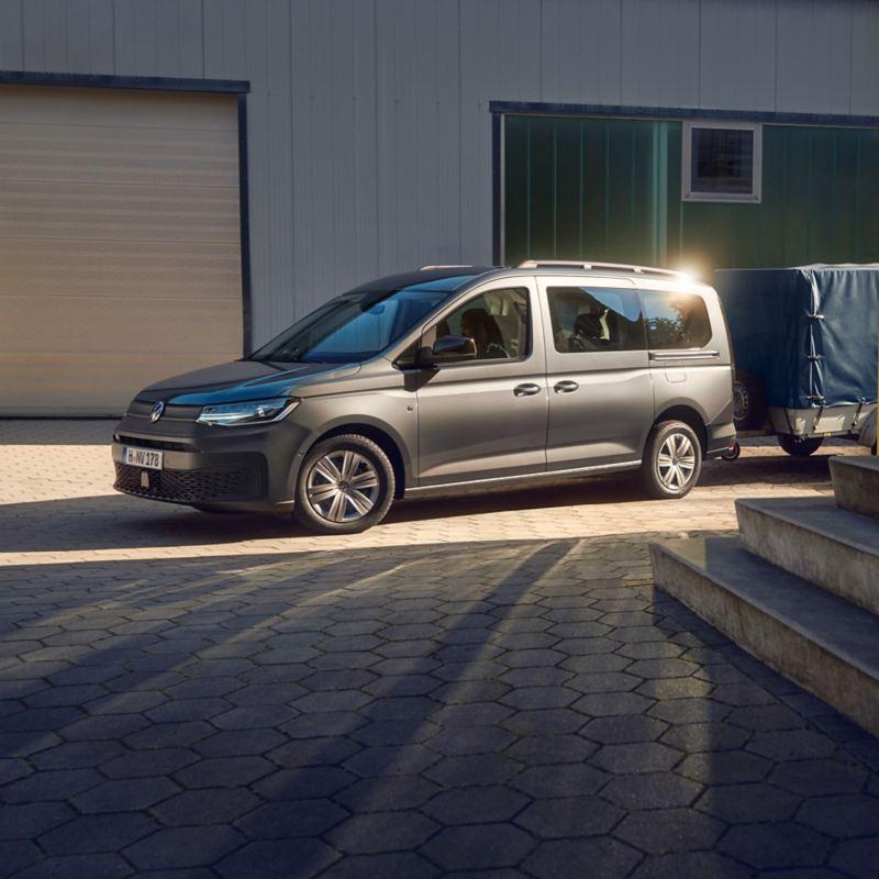 Un break Volkswagen Caddy avec remorque est garé devant un complexe de logements.