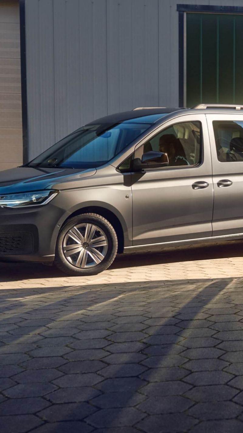 Новый Volkswagen Caddy Kombi с прицепом стоит перед жилым комплексом.