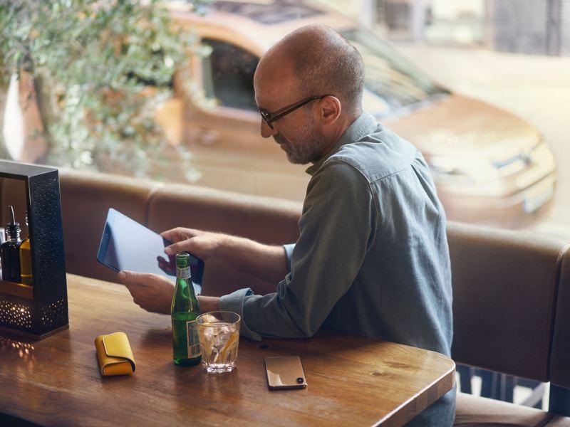 Eine Mann überprüft mit seinem Tablet die Fahrzeugdaten seines Fahrzeugs.