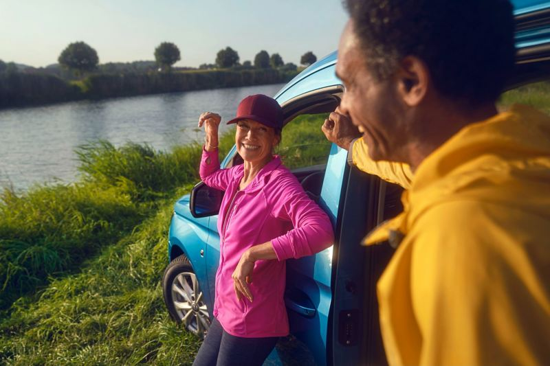 Een man en een vrouw staan te praten voor een nieuwe Caddy die langs een rivier is geparkeerd.