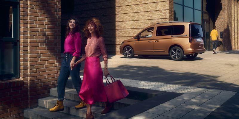 Twee vrouwen lopen. Op de achtergrond staat de nieuwe Caddy.