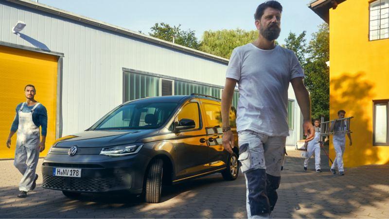 Vier Maler stehen um einen VW Caddy Kombi.