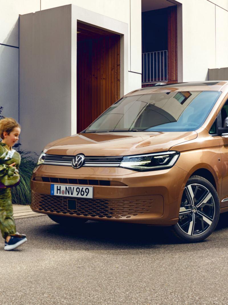 En familj vid en Volkswagen Caddy