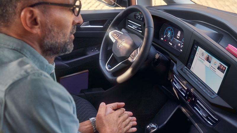Un homme est assis sur le siège passager avant et utilise les services We Connect.