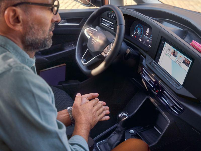 Ein Mann sitzt auf dem Beifahrersitz und bedient die Dienste von We Connect.