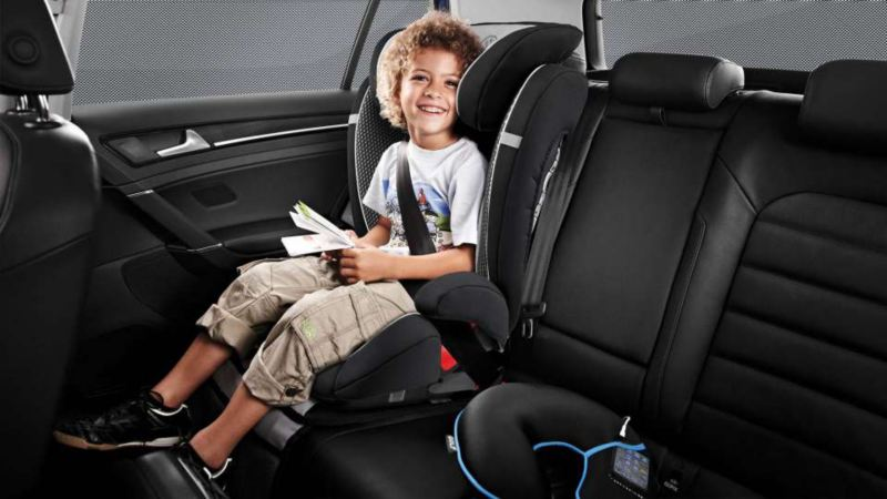 Smiling young child  strapped into Volkswagen child seat