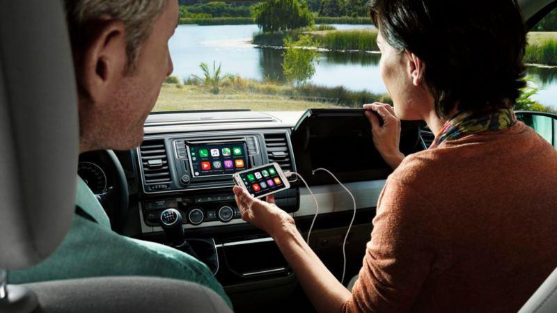 Pareja dentro de un vehículo comercial Volkswagen conectando el móvil con Android Auto