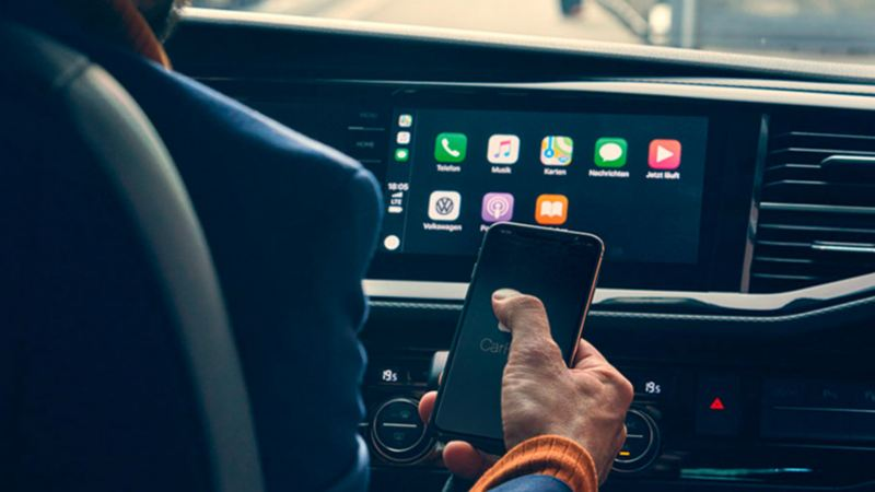 Detalle de un móvill delante de la pantalla de un vehículo comercial mostrando la interfaz de Apple CarPlay