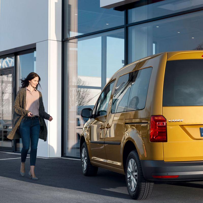 Mujer caminando hacia un Volkswagen Caddy amarillo visto desde atrás