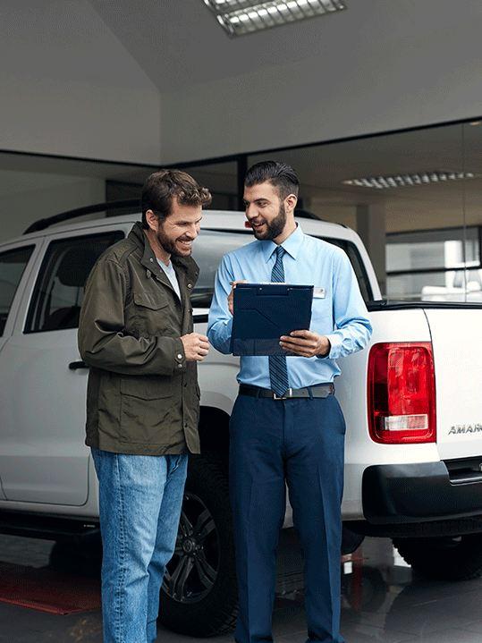 Dos hombres hablando delante de un Amarok en un concesionario Volskwagen
