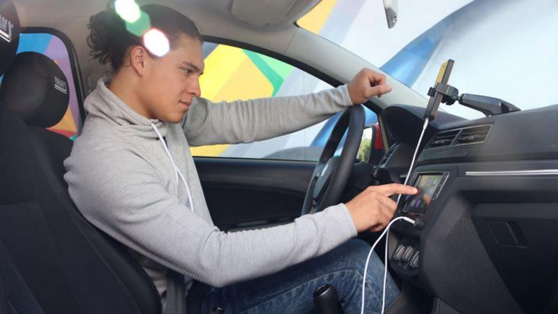 Conductor de auto VW escuchando consejos y tendencias en el podcast Radio Volkswagen