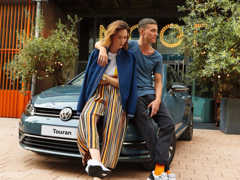 A couple leaning on the front of a VW Golf bonet