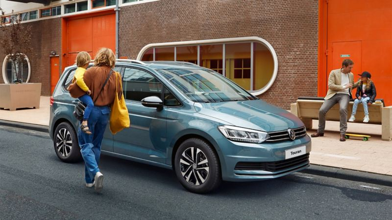 A woman who is about to get in a metallic blue VW Touran while carrying her child