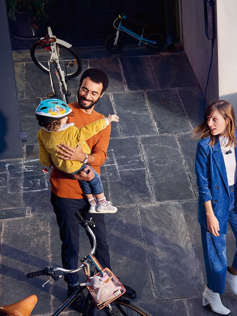 A man holding a child, standing next to a bicycle with a woman nearby