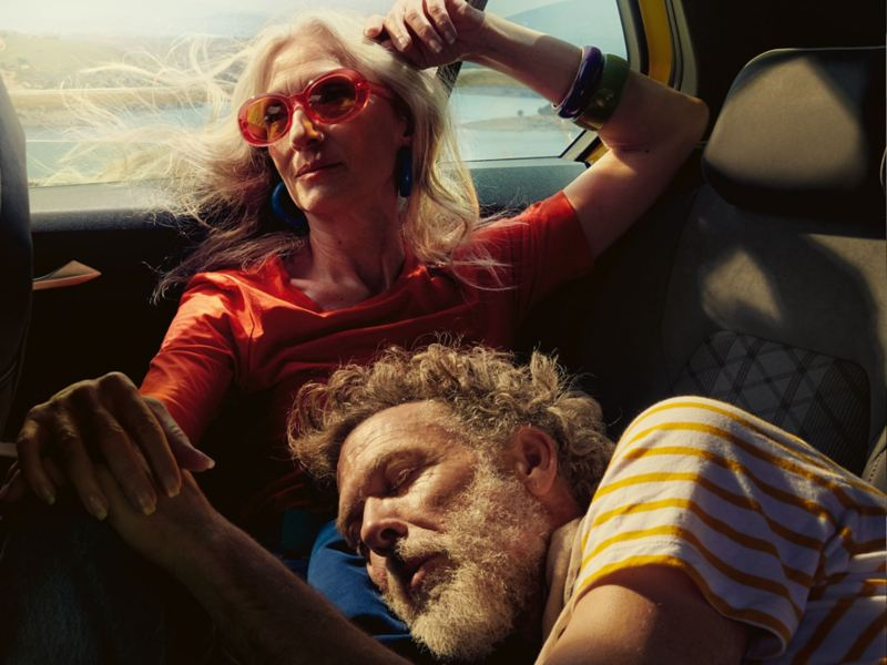 A woman and a man relaxing in the back of VW vehicle