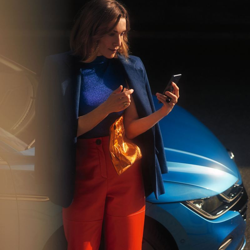 A woman holding a mobile phone leaning on a VW vehicle