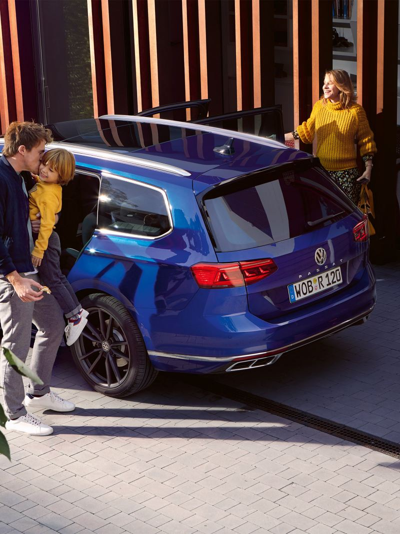 A family standing by a Volkswagen Passat
