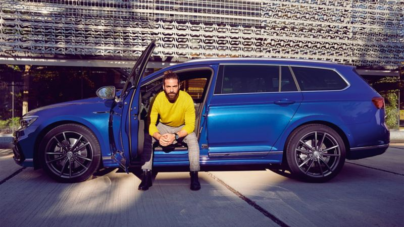 A man sitting with legs outside an opened door of a Volkswagen car