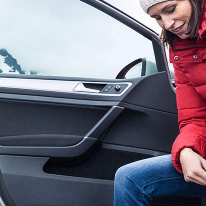 Une femme s'apprêtant à conduire sa Volkswagen, lien vers la page « cout utilisation » de VW