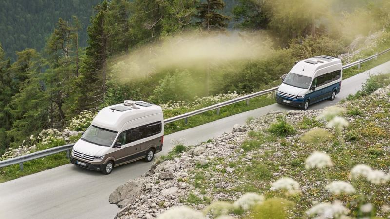 Ein VW Grad California 600 fährt hinter einem VW Grand California 680 eine Bergstraße entlang.