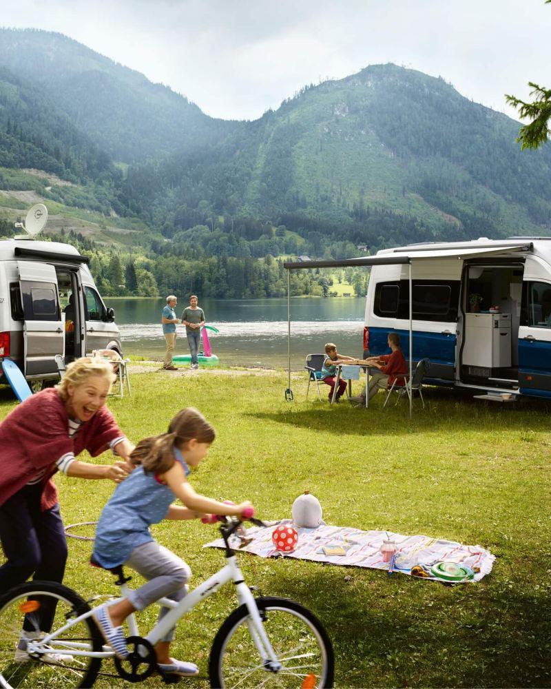 Eine Familie campt mit ihren VW Grand California 600 und VW Grand California 680 am See.