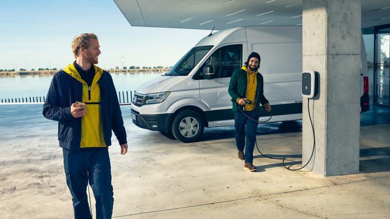 Der Volkswagen e-Crafter steht an einer e-Tankstelle in einer Hafenkulisse.