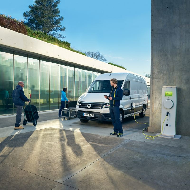 Un Volkswagen e-Crafter dans une situation de tous les jours, à une station de recharge.