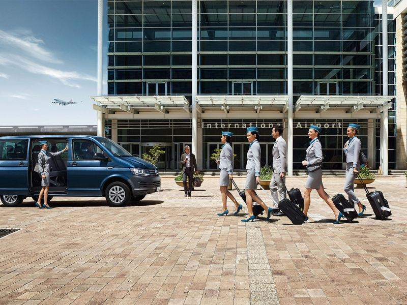 VW Transporter station wagon stands in front of the International Airport, flight attendants get in