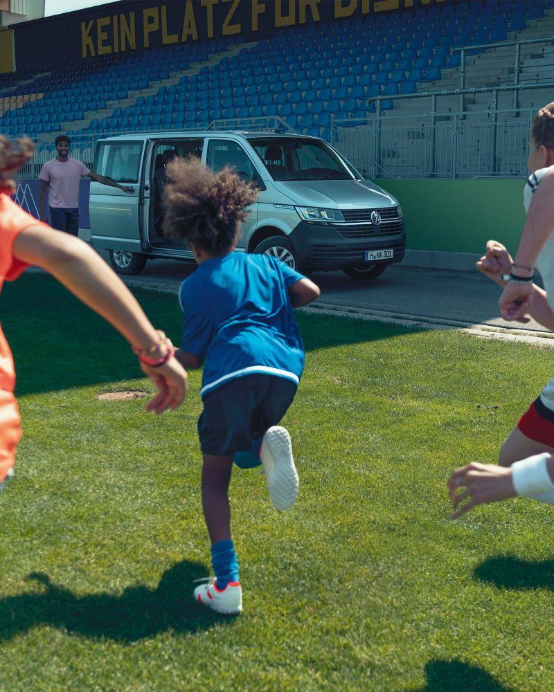 Eine Horde Fußballspielerinnen laufen auf  ihren Trainer zu, der vor einem Volkswagen Caravelle steht.