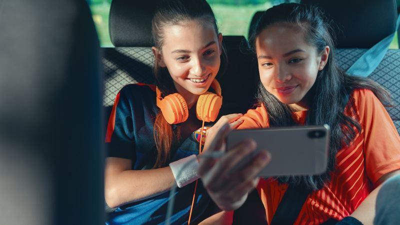 Deux filles sont assises sur le siège arrière et regardent quelque chose sur un smartphone branché.