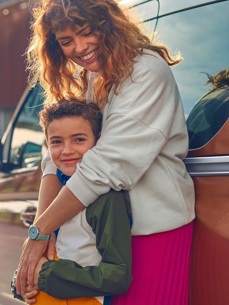 Eine Frau die an einen Volkswagen Caddy angelehnt ist umarmt ein Kind von hinten.