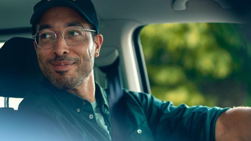 Un homme est assis au volant et regarde par-dessus son épaule en souriant.