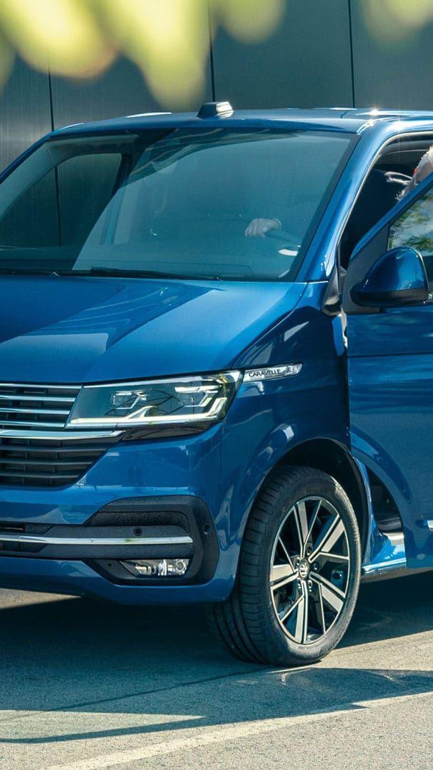 Un uomo scende da un Caravelle Volkswagen, visto 3/4 frontalmente con un primo pianto sulla parte anteriore.