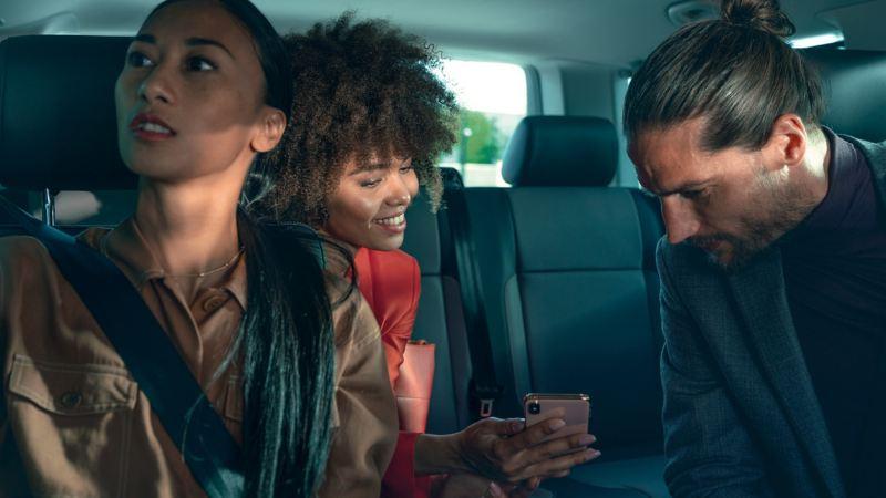 Un homme et deux femmes sont assis dans l'habitacle d'une Volkswagen et regardent l'écran d'un smartphone