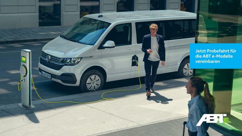 Ein Mann steht vor einem ABT e-Caravelle, der über eine Ladesäule aufgeladen wird.