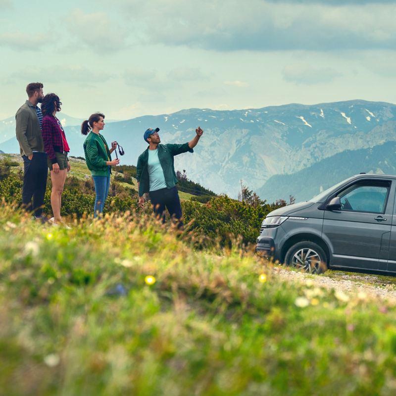 Un groupe de personnes devant une Caravelle Volkswagen dans les Alpes.