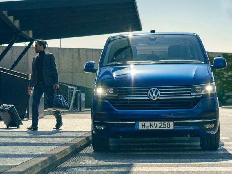 vw Volkswagen blå Caravelle personbil flyplass mann krysser gaten med bag og trillekoffert