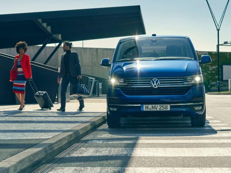 Ein VW Caravelle steht an einem Flughafen, Leute gehen mit Koffer auf dem Gehweg.