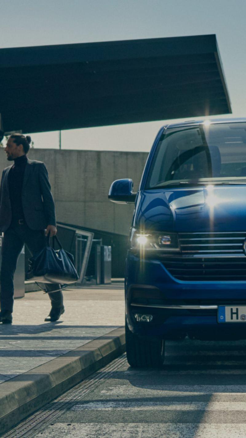 Ein Volkswagen Caravelle 6.1 steht an einem Flughafen. Menschen gehen mit einem Koffer auf dem Gehweg.