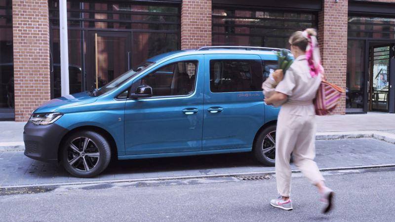 Bildet viser en blå Volkswagen Caddy California Maxi mini camper som står parkert i et bysentrum og en dame som går mot bilen med matvarepose i armene