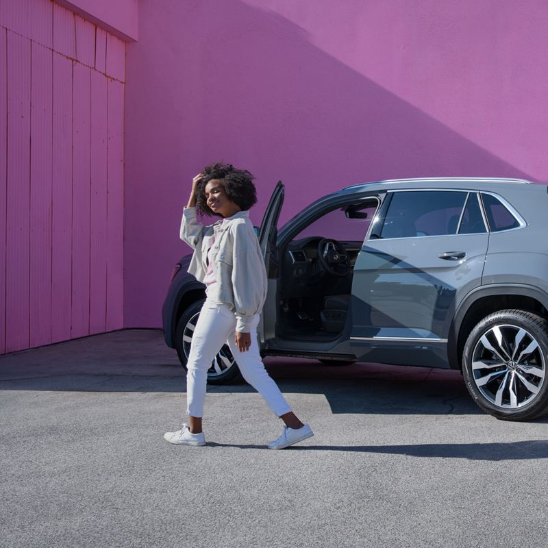 """Woman standing in front of VW Atlas Cross Sport SUV, link out to the """"be the change"""" page"""