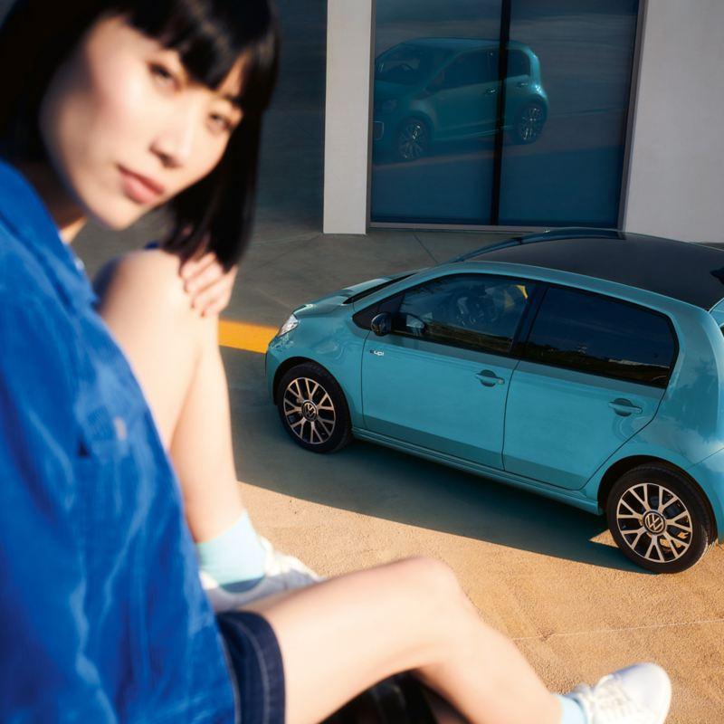 Nainen istuu muurilla pysäköidyn e-up!-auton yllä ja katsoo kameraan
