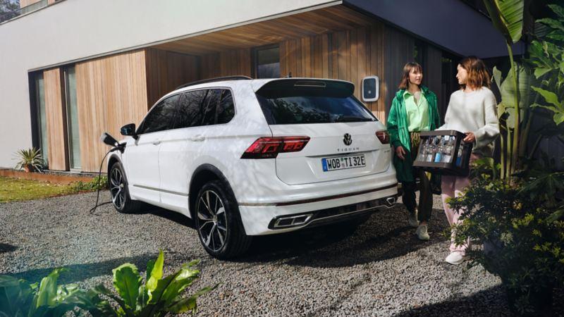Due donne si avvicinano al bagagliaio di una Volkswagen Tiguan eHYBRID in carica per riporre delle bottiglie di vetro.