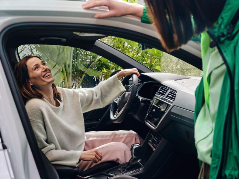 Una donna seduta alla postazione di guida della Volkswagen Tiguan eHYBRID chiacchiera con un'amica.