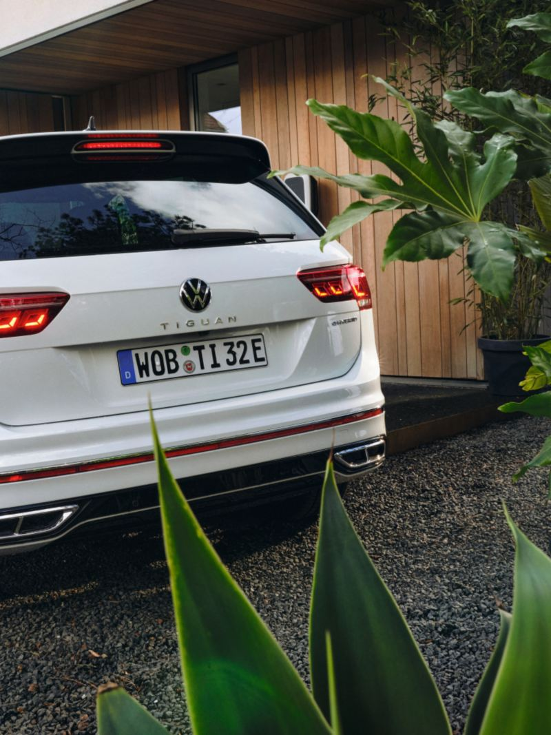 Vista posteriore di Volkswagen Tiguan eHYBRID, parcheggiata accanto alla postazione di ricarica di un'abitazione